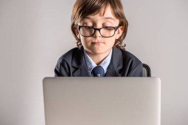 Schoolchild in business suit using laptop