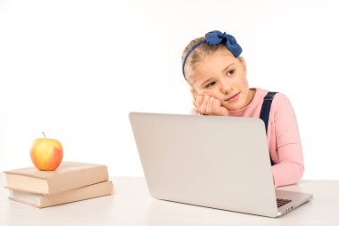 Thoughtful schoolgirl sitting at desk with laptop stock vector