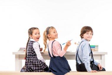 Smiling schoolchildren sitting at desk
