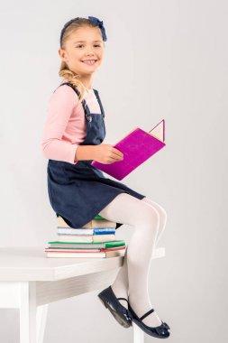 Smiling schoolgirl holding book