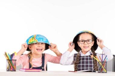 Schoolgirls with halves of globe on heads