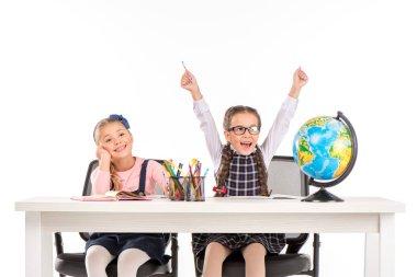 Happy schoolgirls sitting with globe