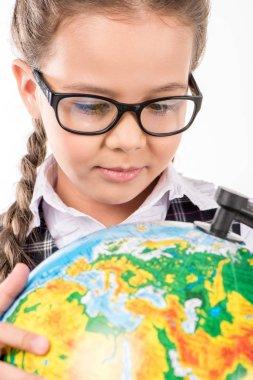 Schoolgirl looking at globe