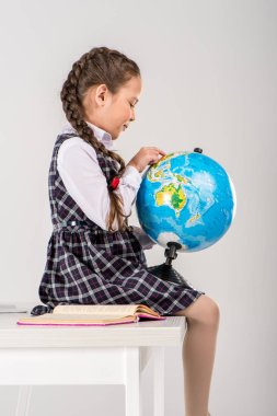 Schoolgirl exploring world on globe