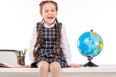 Happy schoolgirl sitting  with globe