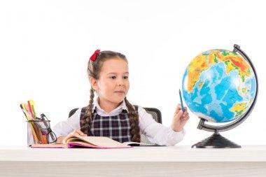 Schoolgirl doing homework and using globe