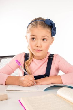 Serious schoolgirl writing her homework