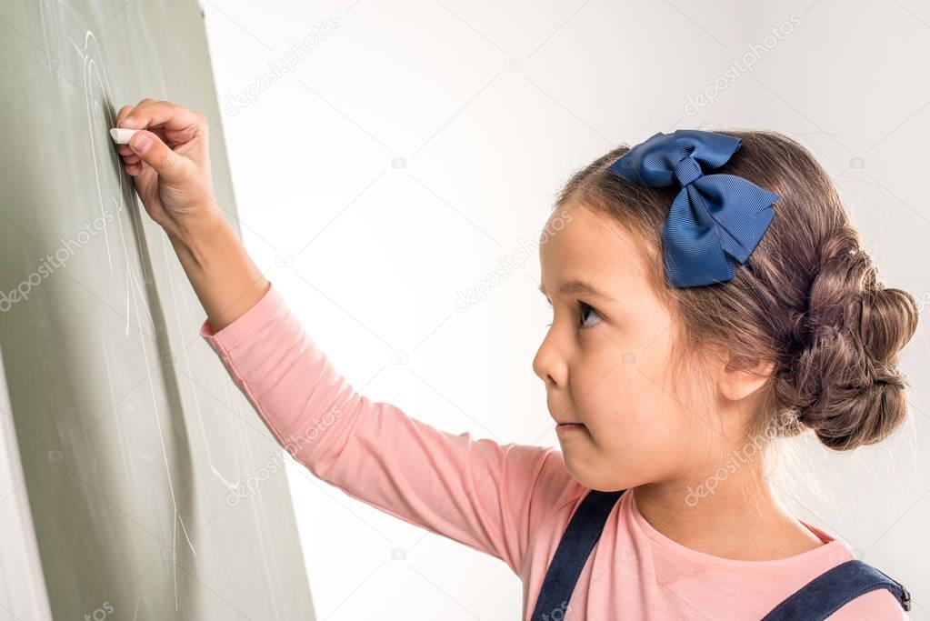 Schoolgirl drawing on blackboard