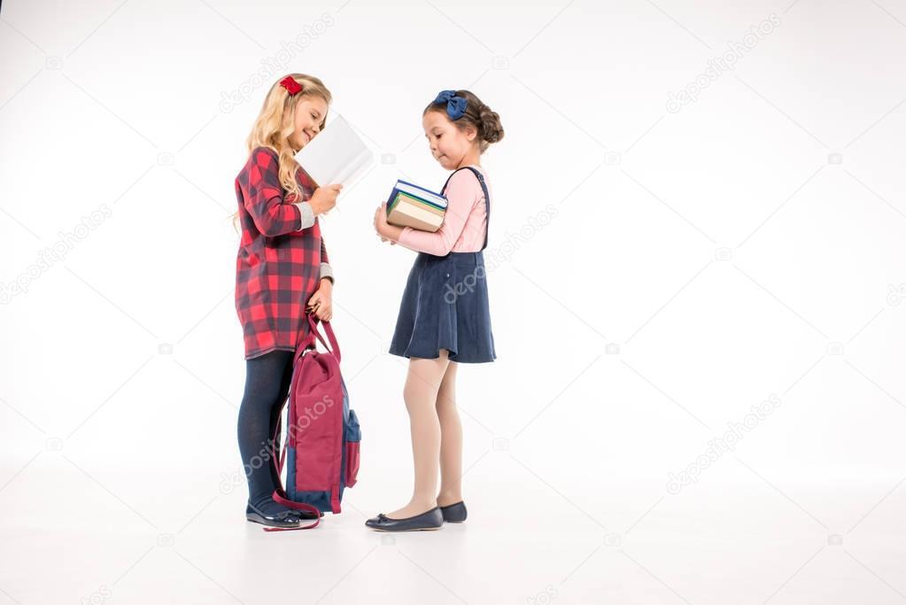 Smiling schoolgirls standing with books