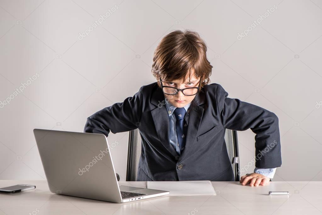 Schoolchild in business suit standing over desk