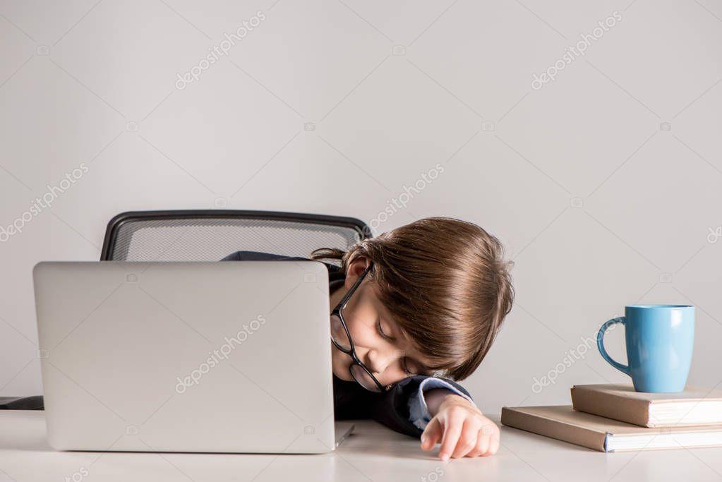 schoolchild in business suit sleeping on desk