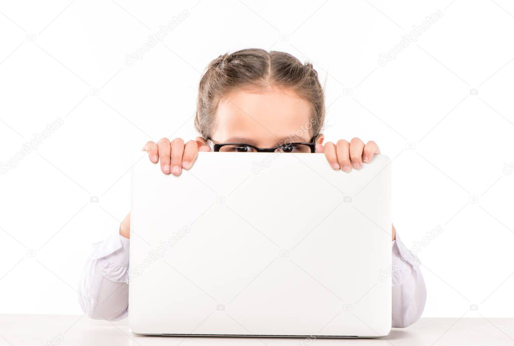 Schoolgirl hiding behind laptop