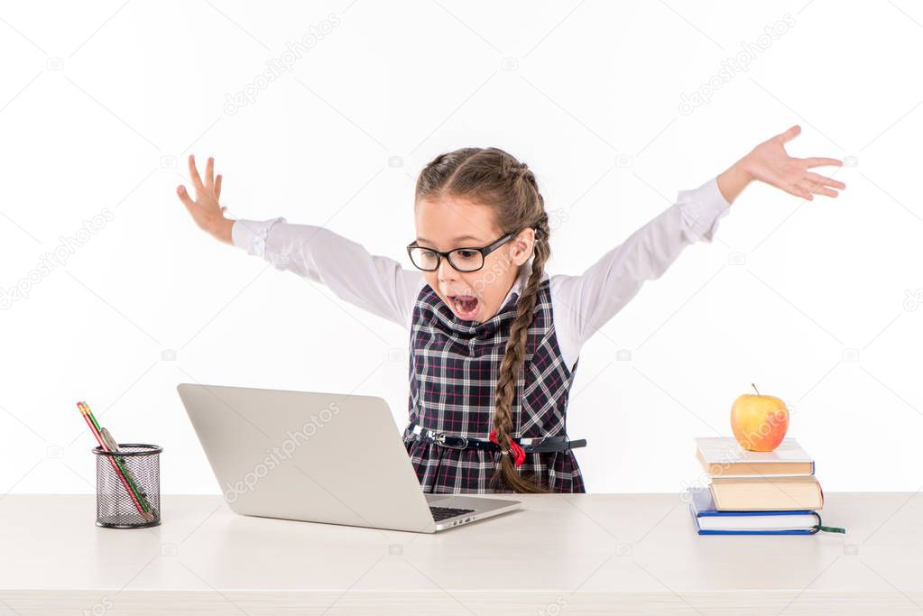 Schoolgirl at desk with laptop