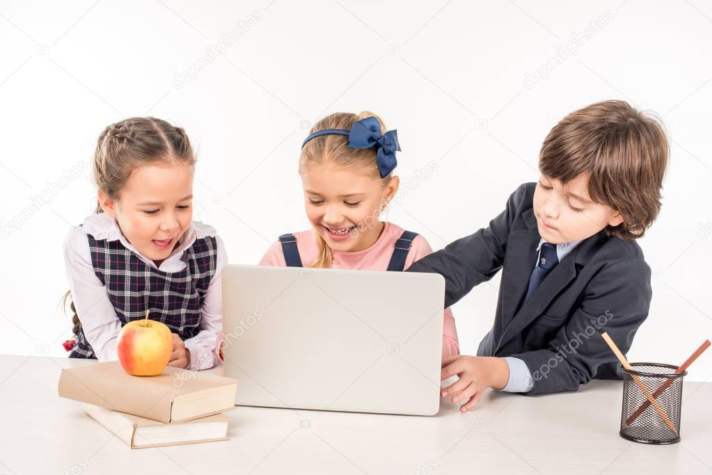 Smiling classmates sitting at desk and using laptop stock vector