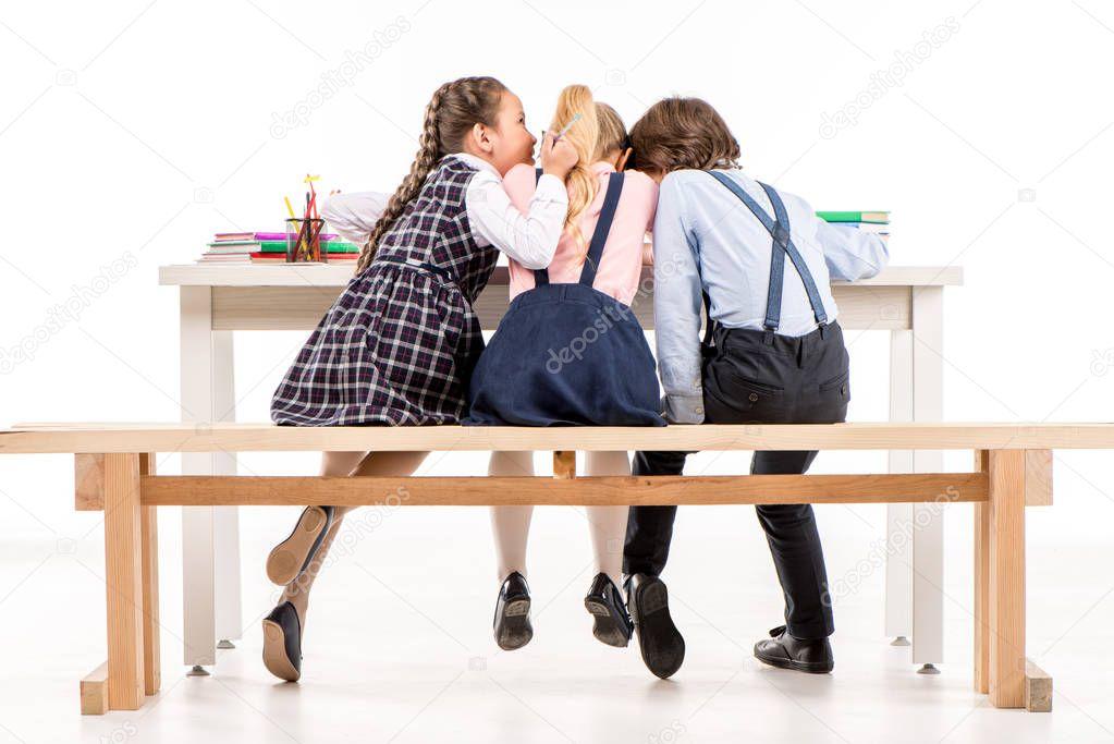Schoolchildren sitting at desk and talking