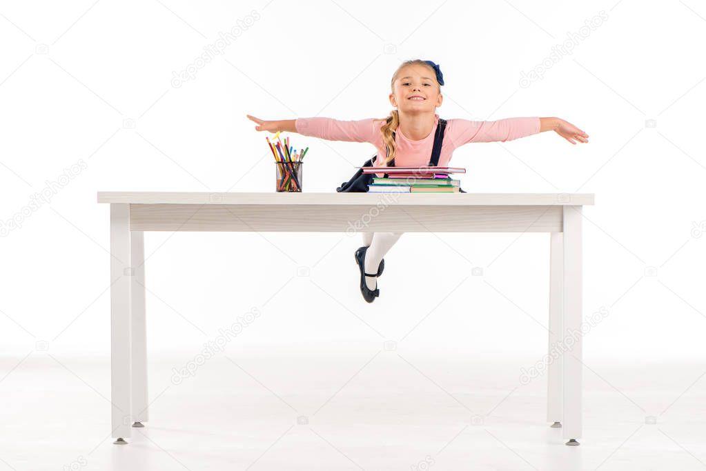 Cheerful schoolgirl lying on desk