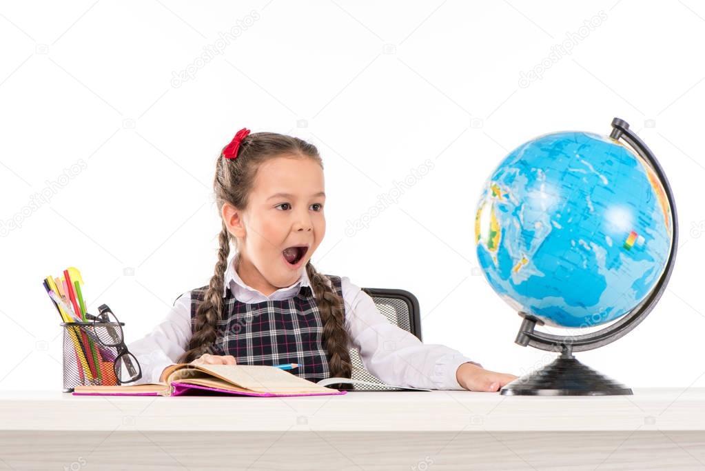 Shocked schoolgirl looking at globe