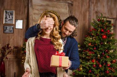 Man giving christmas present to woman