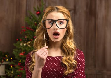 Surprised woman holding party glasses