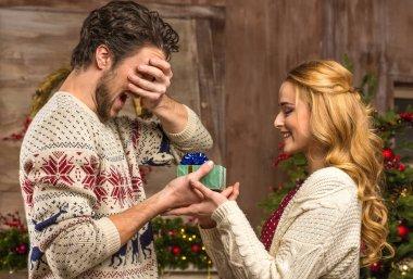 Woman giving christmas present to man