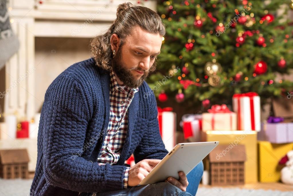 Thoughtful man using digital tablet