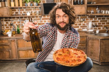 Man with beer and pizza
