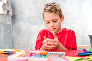Schoolchild playing with plasticine