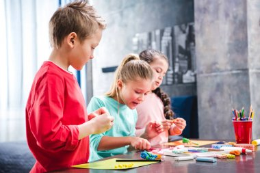 Schoolchildren playing with plasticine