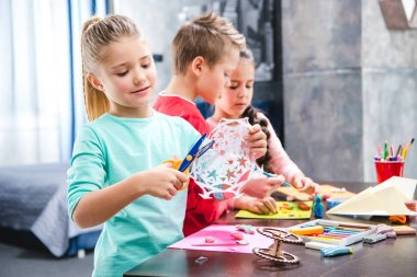 Kid cutting snowflake from paper