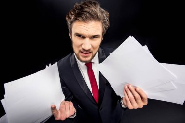 Annoyed businessman holding papers
