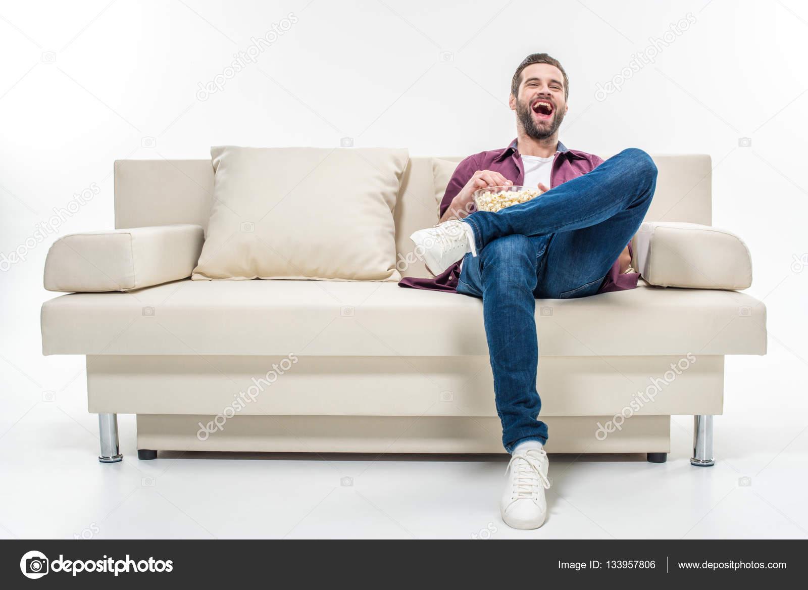 Hombre sentado en el sof con las palomitas de ma z for 3 on a couch