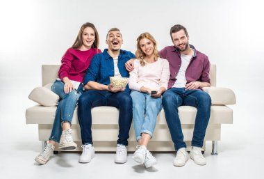 Smiling friends sitting on couch