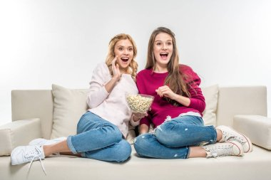 Friends eating popcorn on couch