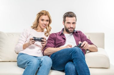 Smiling couple playing with joysticks