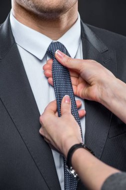 Woman adjusting neck tie