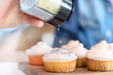 Woman putting confetti on cupcakes