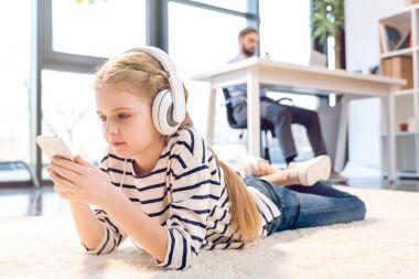 Daughter using smartphone and headphones