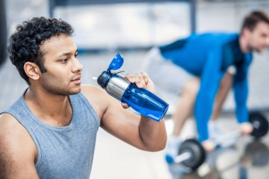 Man with bottle of water resting at gym