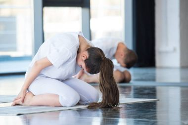Woman in child pose Balasana with instructor