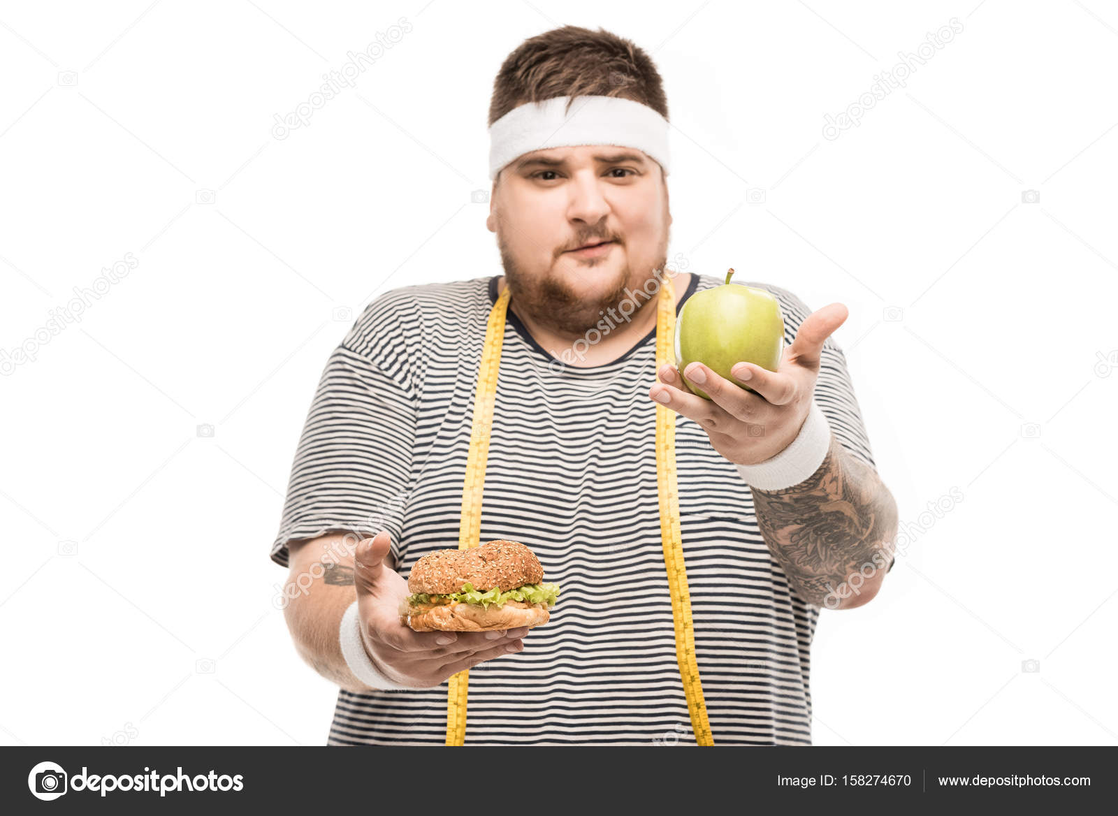 Young chubby man looking at camera while holding burger and apple isolated  on white — Photo by ...