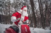Fotografie Santa Claus sitting on red scooter