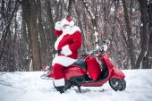 Weihnachtsmann sitzt auf rotem Roller