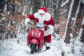 Photo Santa Claus riding red scooter