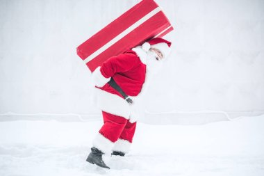 Santa Claus carrying gift box