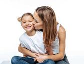 Fotografie Mutter zu umarmen und küssen lächelnd Tochter
