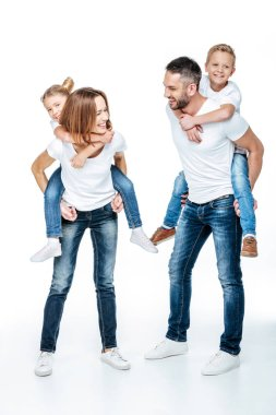 Parents piggybacking happy children