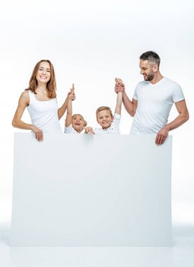 Smiling family holding blank card