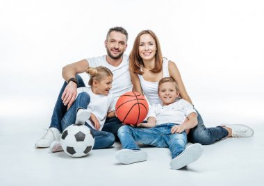 Cheerful family with soccer and basketball balls