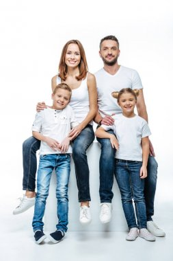 Happy parents with children in white t-shirts