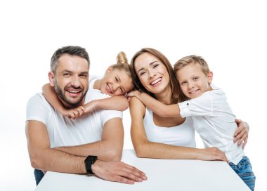 Smiling family in white t-shirts hugging